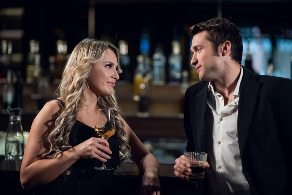 ein schönes Liebespaar trinkt einen Drink an der Bar