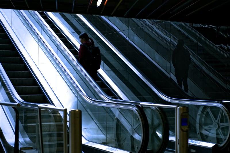 eine Frau auf der Rolltreppe