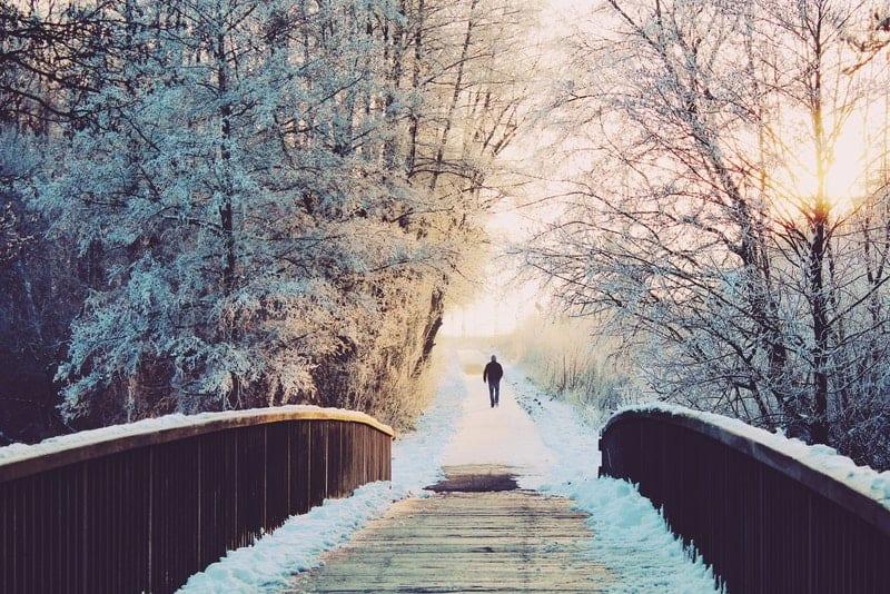 eine Holzbrücke und in der Ferne ein Mann, der geht