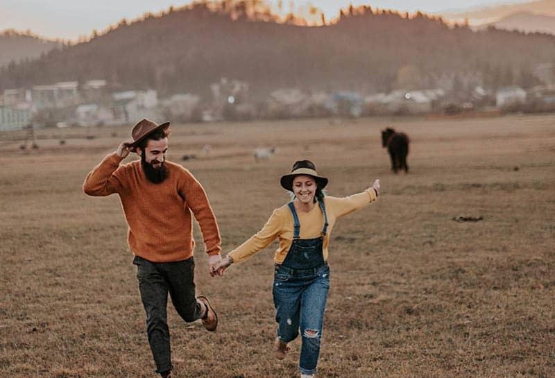 glückliches Paar, das auf Feld im Dorf läuft