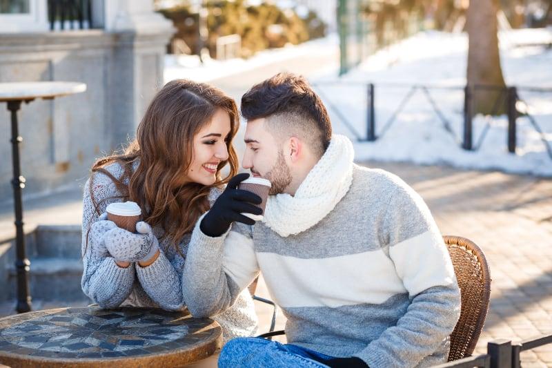 lächelndes Paar, das Sweatshirt und Handschuhe trägt, während Tasse Kaffee im Straßencafé hält
