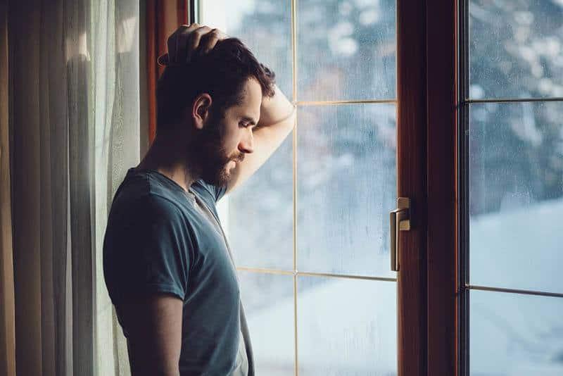 nachdenklicher Mann, der nahe Fenster zu Hause steht