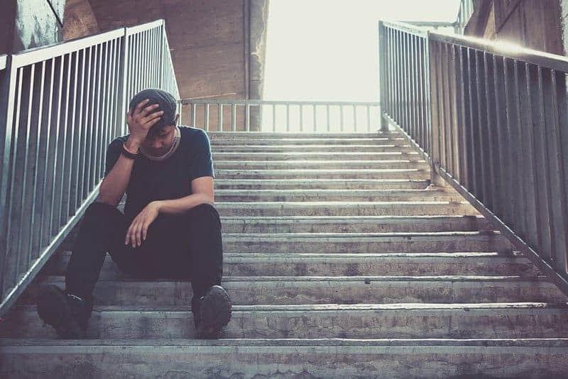 trauriger Mann, der draußen an der Treppe sitzt