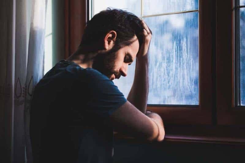trauriger Mann, der seinen Kopf vor Fenster hält