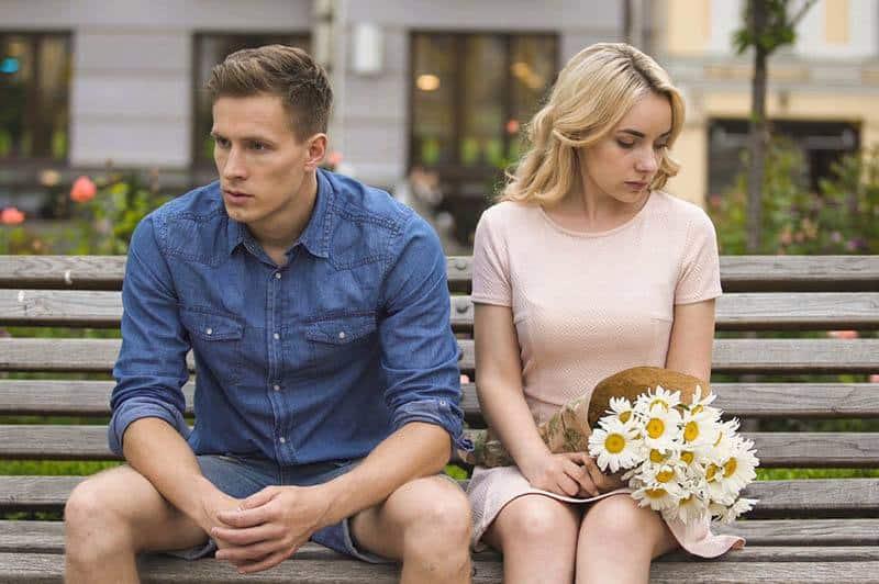 verärgertes Paar, das auf Parkbank sitzt und gegenüber schaut