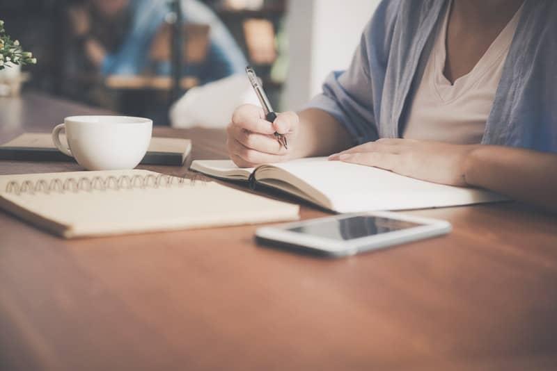 Die Frau am Tisch sitzt und schreibt