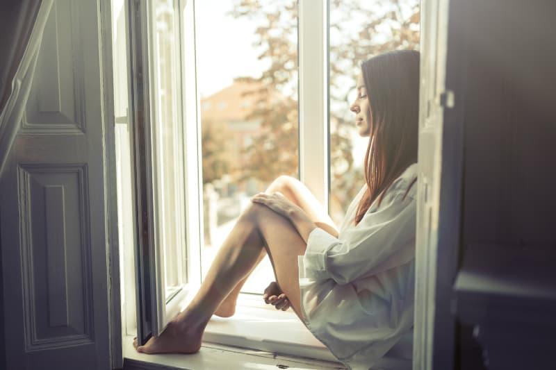 Ein Mädchen in einem weißen Hemd sitzt auf einem Fensterbrett