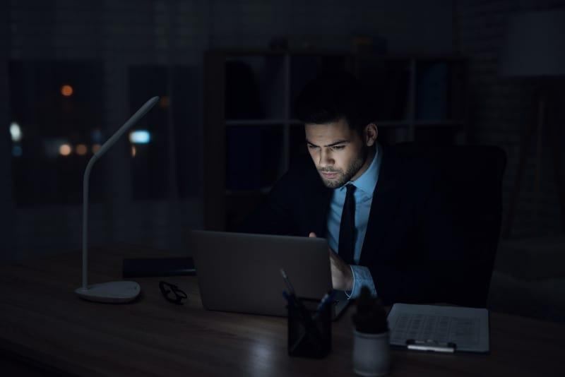 Ein Mann, der in einem dunklen Büro an einem Laptop arbeitet