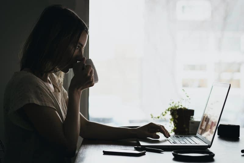 Frau, die Kaffee und Knopf auf Laptop trinkt