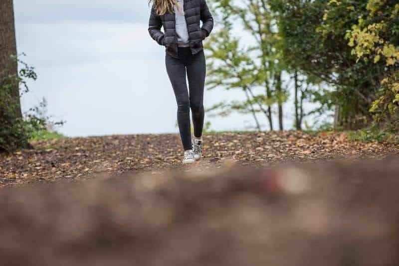 Frau, die schwarze Jeans und schwarze Jacke trägt, die draußen gehen