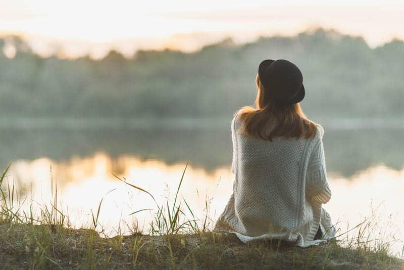 Frau, die schwarzen Hut trägt und vor See sitzt