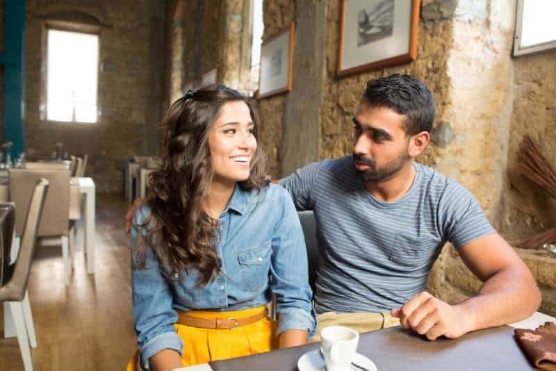 Junges Paar, das im Restaurant und im Café spricht
