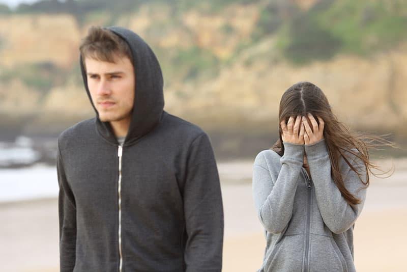 Mann geht von weinender Frau