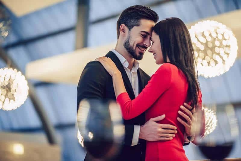 Mann im Anzug und Frau im roten Kleid umarmen sich