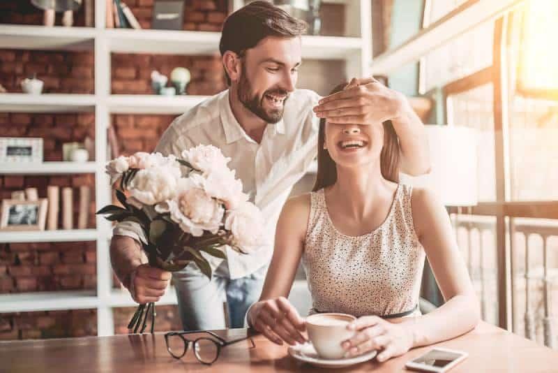 Mann präsentiert seiner Freundin Blumen
