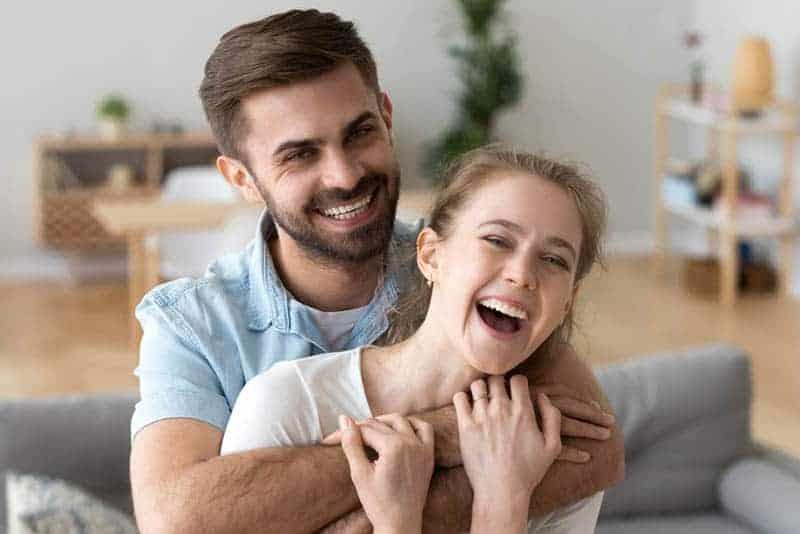Mann umarmt Frau von hinten