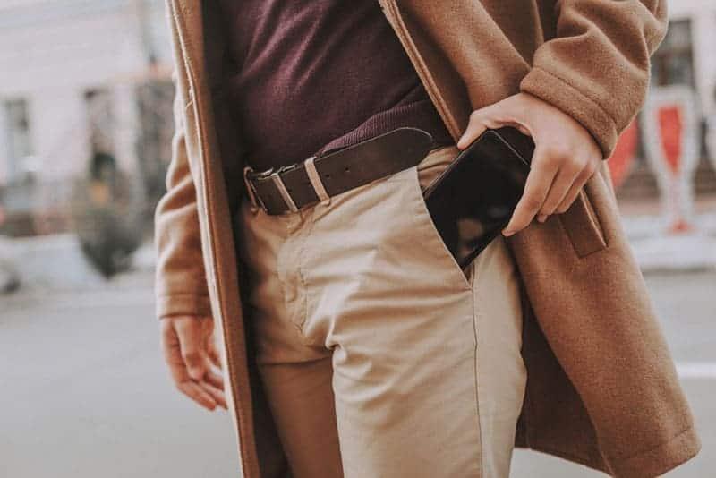 Nahaufnahmefoto des Mannes, der sein Telefon in die Tasche steckt