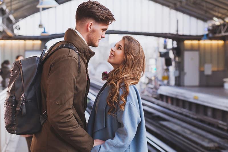 Paar hält ihre Hand und schaut sich am Bahnhof an
