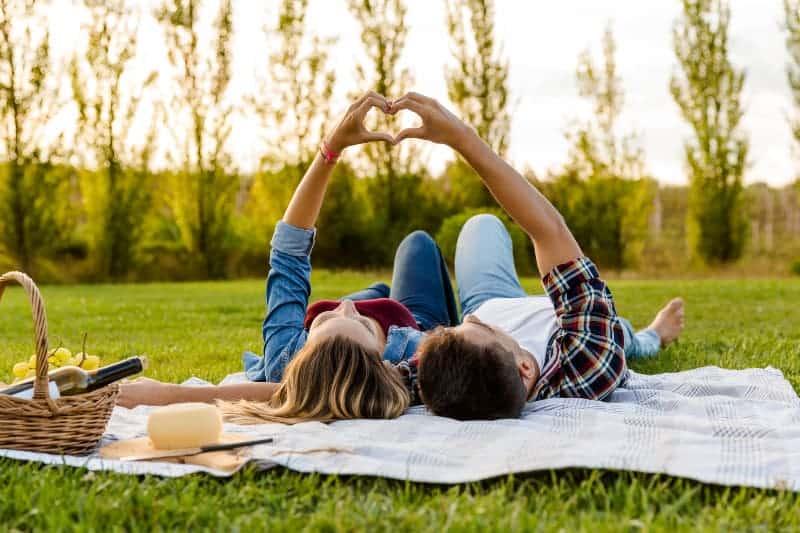 Paar machen Herz, während auf Gras liegen