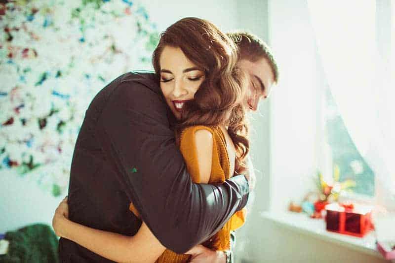 Paar umarmt sich zu Hause