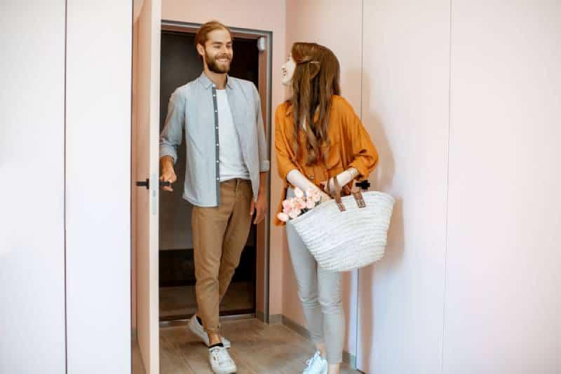 Schönes junges Paar, das nach Hause kommt und zusammen im rosa Korridor der modernen Wohnung geht