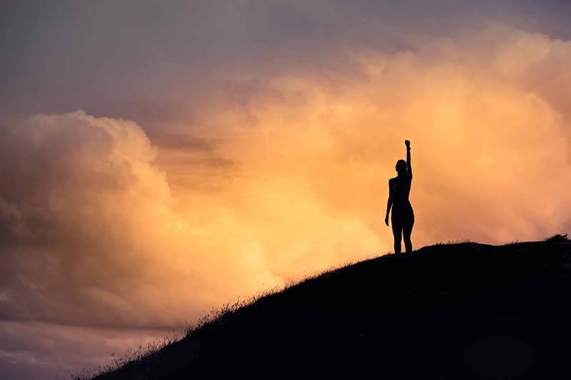 Silhouette der Frau, die ihre Hand im Himmel erhebt
