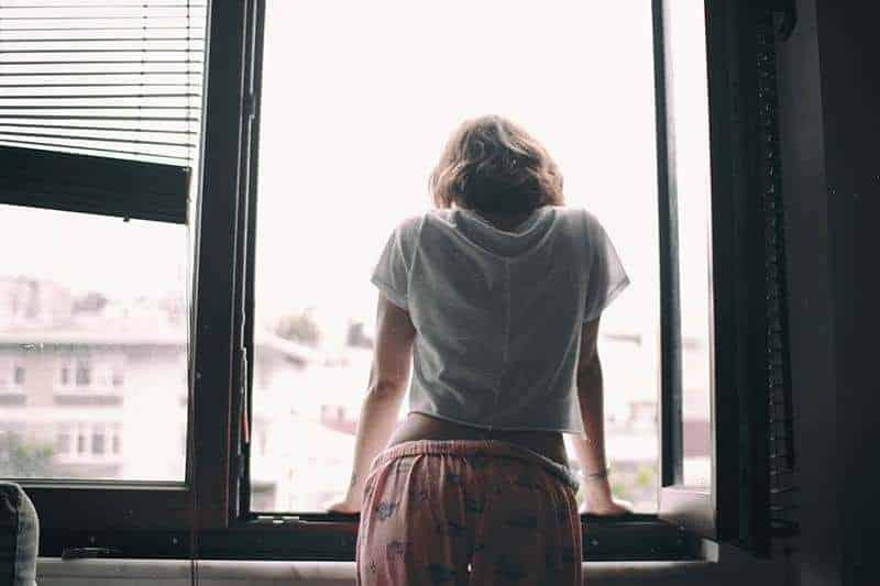 Rückansicht der Frau, die sich auf Fenster lehnt, die Pyjamas tragen