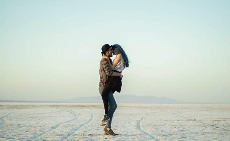 ein Mädchen, das von einem Jungen in den Armen in der Wüste getragen wird