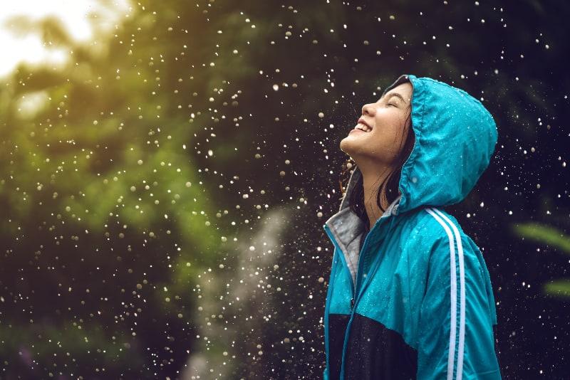 ein Mädchen, das im Regen einen Regenmantel trägt