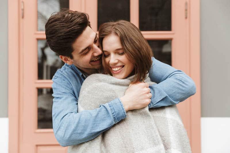 glückliches schönes Paar, das draußen umarmt