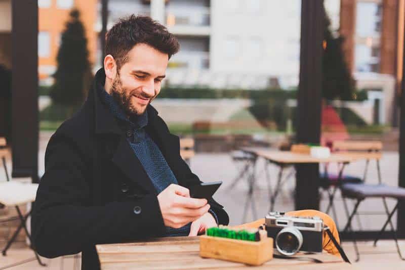 lächelnder Mann, der schwarzen Mantel trägt und auf seinem Telefon im Straßencafé tippt
