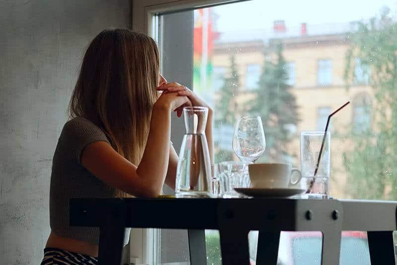 nachdenkliche Frau, die durch Fenster im Café schaut