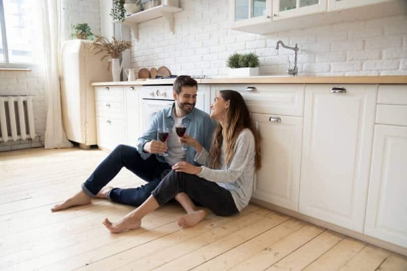 romantisches Paar, das auf Küchenboden sitzt und Wein trinkt, während sie sich lächelnd ansehen