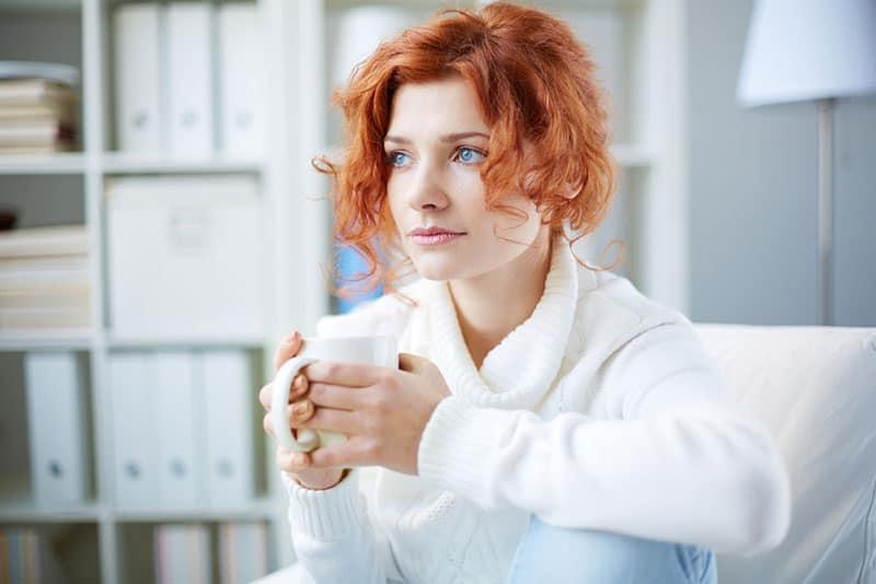 schöne Frau mit roten Haaren und blauen Augen, die Kaffee trinken