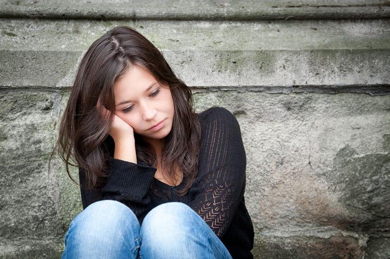 traurige Frau, die draußen sitzt