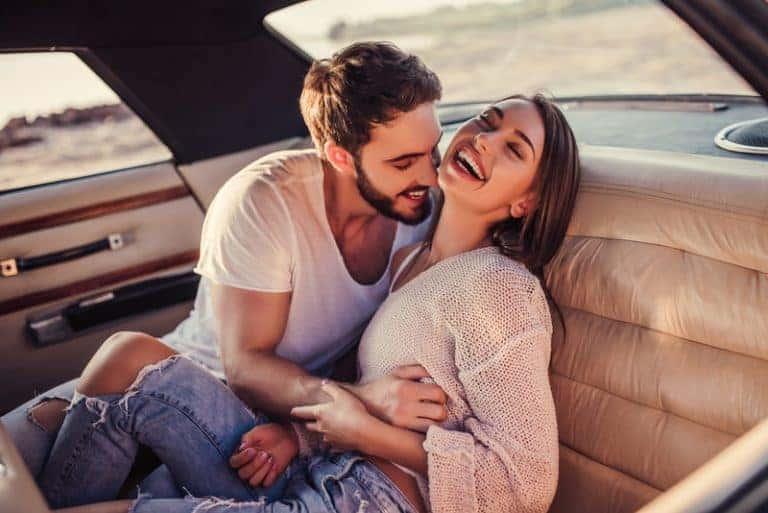 Paar lächelt und genießt im Auto