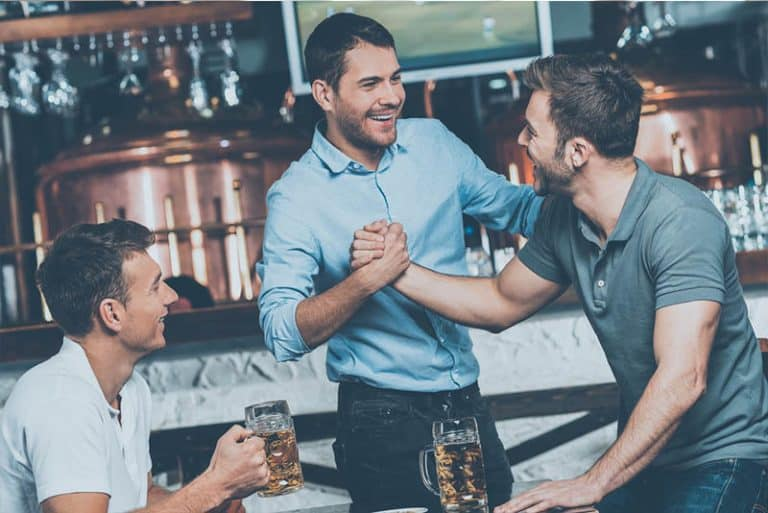 Drei Freunde begrüßen sich an der Bar