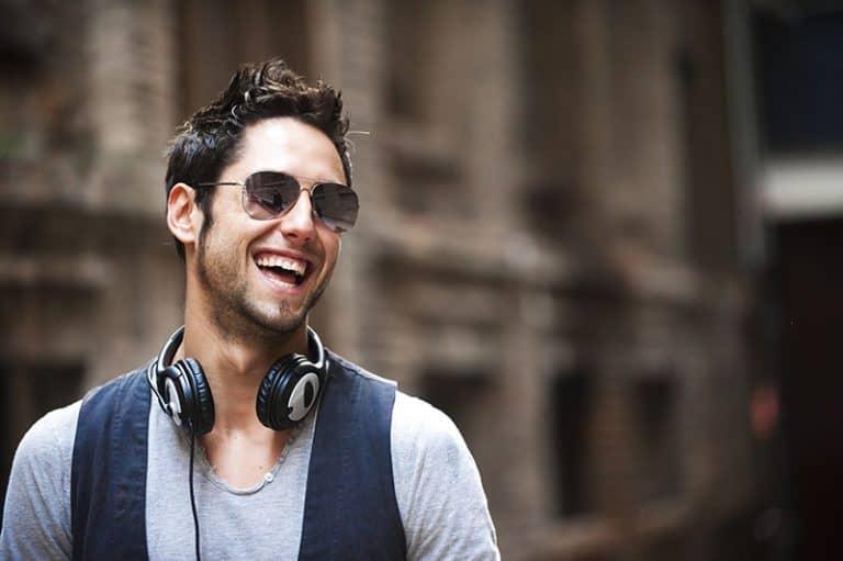 Ein Mann, der lacht und Kopfhörer um den Hals hat