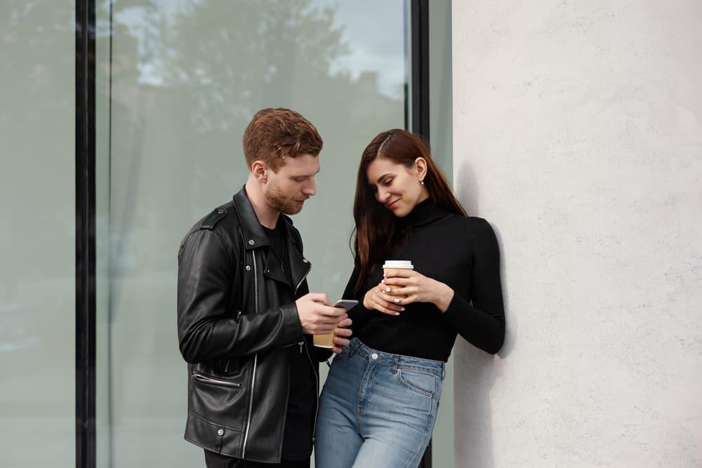 Ein Mann in einer schwarzen Jacke spricht mit einem lächelnden Mädchen