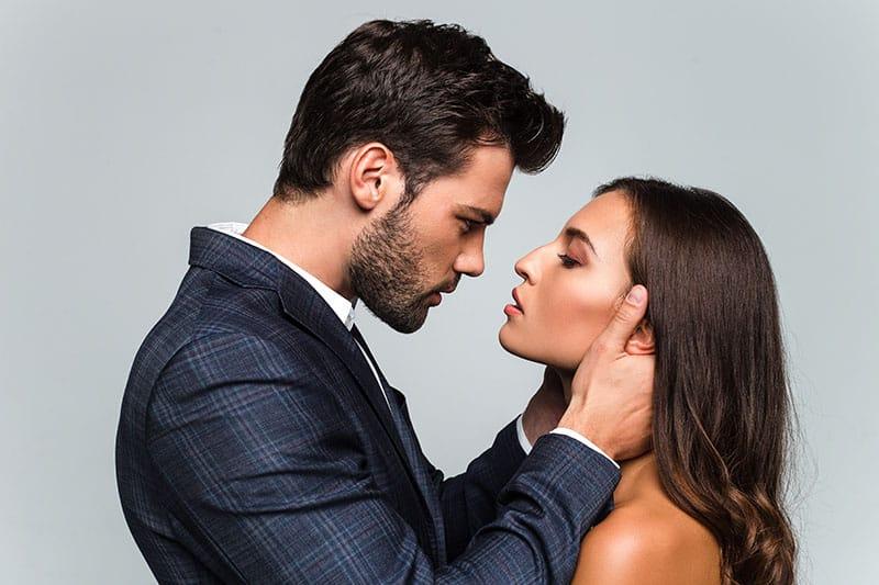 Ein Mann mit Bart hält seine Frau am Kopf