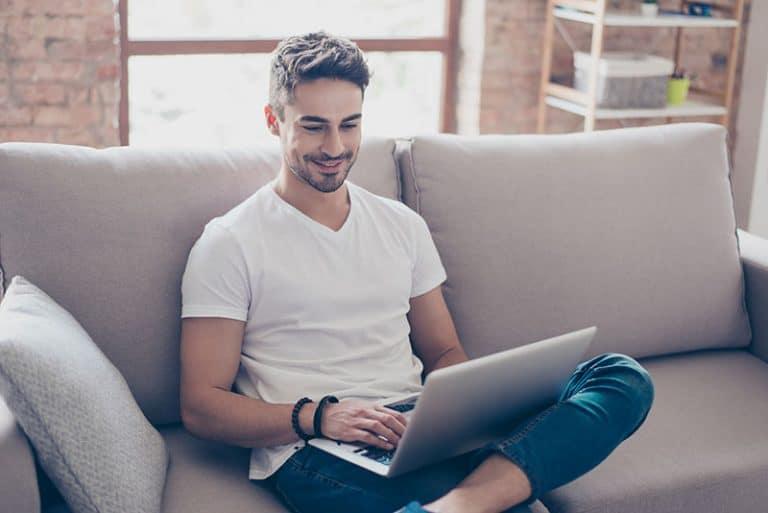 Ein Mann sitzt auf einer Couch und arbeitet an einem Laptop