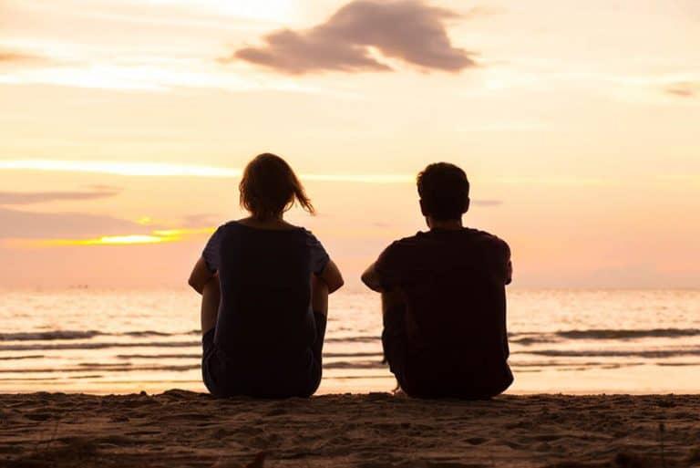 Ein Paar beobachtet den Sonnenuntergang am Strand