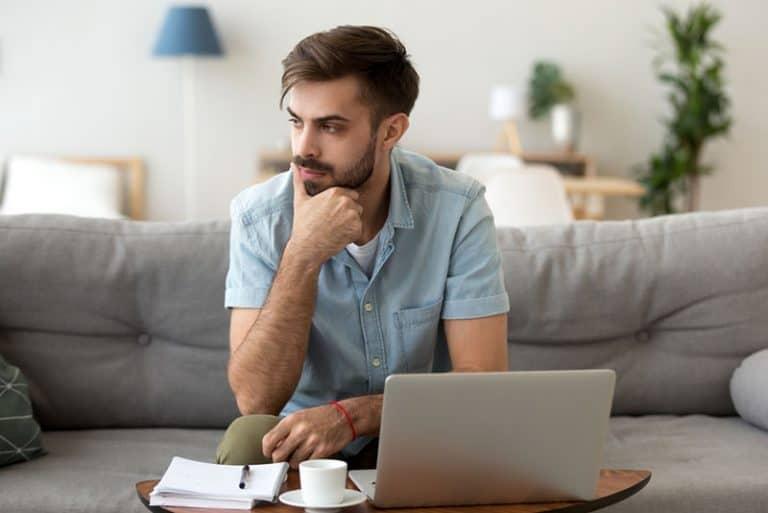 Ein besorgter Mann sitzt im Wohnzimmer neben einem Laptop