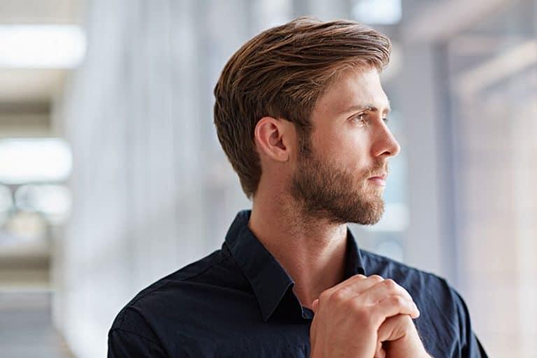 Ein braunhaariger Mann mit Bart schaut aus dem Fenster