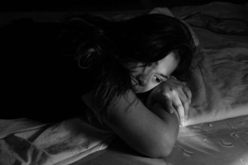 Ein traurigesMadchen liegt auf dem Bett