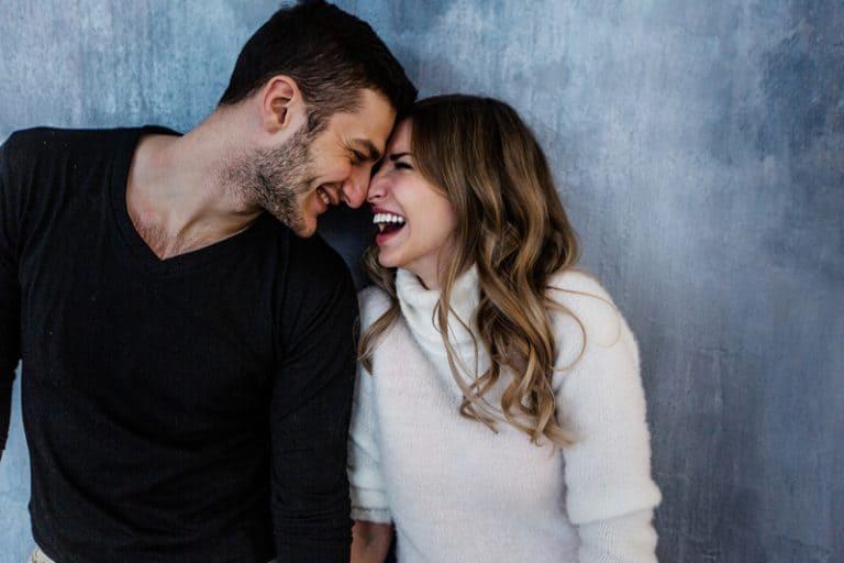 Frau im weißen Pullover, der mit Mann lächelt