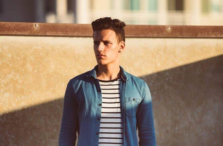 Mann im blauen Hemd, das in der Sonne aufwirft