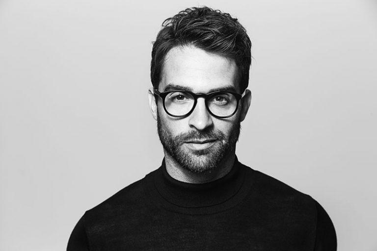 Ein Mann in einem schwarzen Rock und einer nerdigen Brille