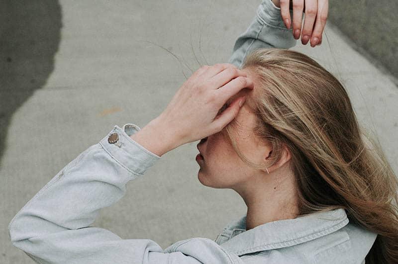 junge blonde Frau, die ihre Haare berührt