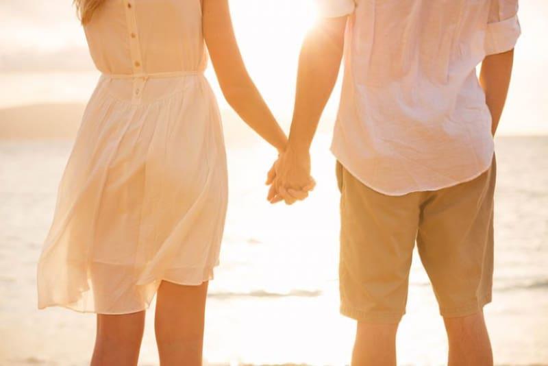 ein Paar, das Händchen haltend am Strand entlang geht